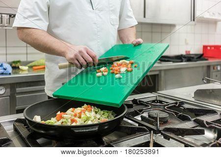Chef in restaurant kitchen preparing vegetables in pan on stove