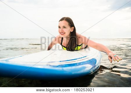 Woman surfer paddling prone on surfboard to the open sea for surfing