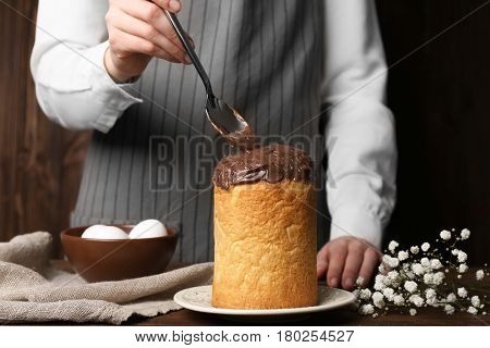Woman decorating Easter cake with chocolate coating on table