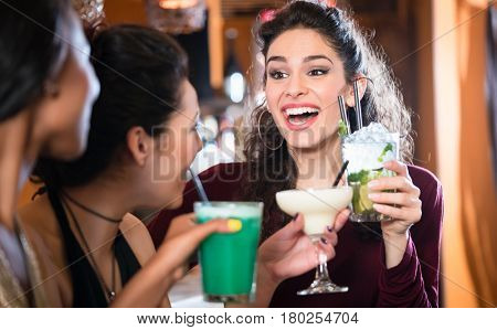 Attractive girls on night out drinking Cocktails and chatting in bar or club