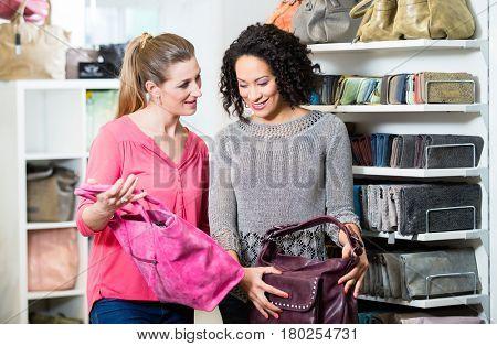 Girlfriends in fashion store buying handbag