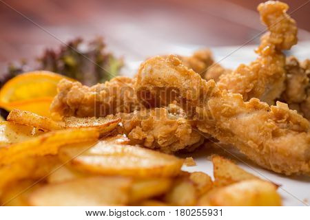 close up of chicken strips with fried potatoes
