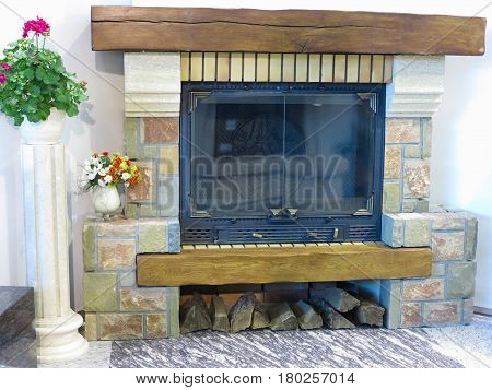 Luxury fireplace with firewood and flower vase decorations.