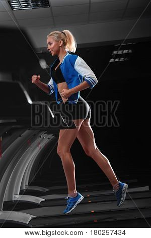 Vertical full length portrait of a fit and strong muscular female athlete wearing sports gear running on a treadmill at the fitness studio healthcare lifestyle energetic activity hobby sportsperson .