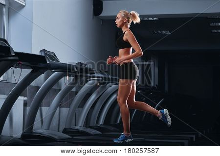 Horizontal full length shot of an attractive fit young woman with perfect strong muscular body wearing sports top and shorts jogging on a treadmill at the health club diet slimming toning motivation .