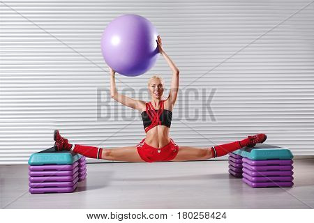 Horizontal shot of a happy female gymnast doing splits at her fitness studio smiling to the camera holding a fit ball over her head sports flexibility stretching body strength confidence gymnastics .