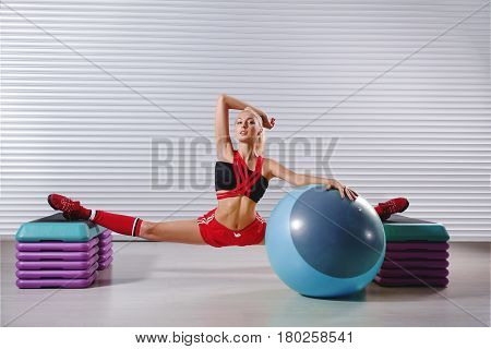Beautiful young female gymnast posing sensually while doing splits lifestyle femininity sexuality athletics physique body power strong confident balancing toned fit sportsperson professional