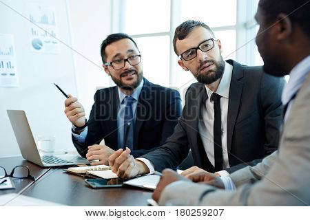 Confident business partners discussing new contract terms before signing it while gathered together in modern meeting room, waist-up portrait
