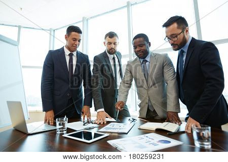 Portrait of middle-aged Afro-American businessman in suit standing in meeting room and pointing at document lying on table, his male colleagues looking at it with interest