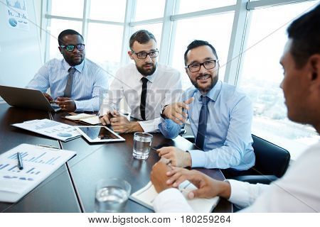Three bearded employees in eyeglasses conducting negotiations with their business partner while sitting in modern meeting room