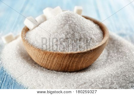 White sand and lump sugar in wooden bowl, close up