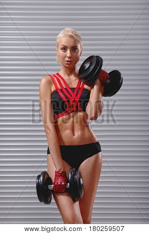 Vertical portrait of a gorgeous young sportswoman in workout gear lifting dumbbells exercising at the gym bodybuilding muscles toning shaping strength power lifestyle personal trainer working out.
