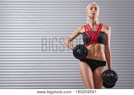 Horizontal shot of a beautiful fitness woman lifting weights gorgeous sportswoman in top and shorts exercising with dumbbells copyspace sports motivation healthcare body sexy hot toning concept.