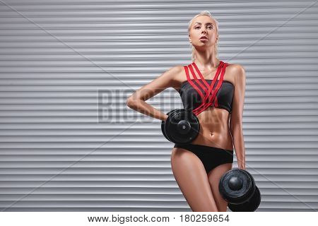 Stunning female fitness model with gorgeous sexy hot toned fit body holding dumbbells looking seductively to the camera copyspace sport fitness shaping toning abs gym healthcare concept.