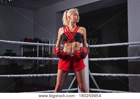 Horizontal shot of an attractive female wearing boxing gloves standing on a boxing ring workout gear equipment professional sportswoman fighter strength power confidence motivation concept