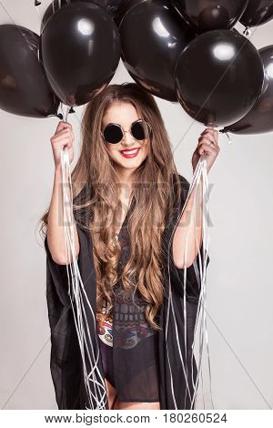 Happy beautiful girl with baloons in her hands posing for camera on a white background. Girl with long hair and red lips wearing combination and glasses.