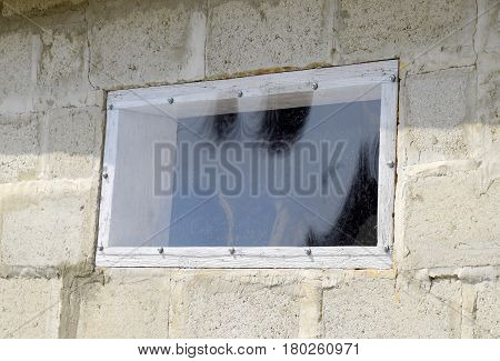A Window Made Of Plexiglas In A Concrete Wall
