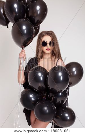 Long-haired girl wearing glasses holding a lot of baloons. Girl on a white background.