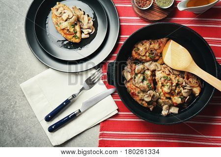 Frying pan with delicious chicken marsala on table