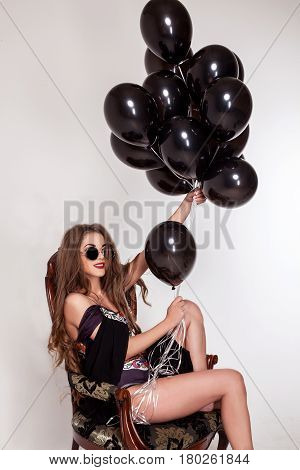 Attractive young woman with a bundle of baloons in her hand posing for camera in an armchair on a white background.