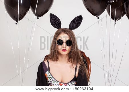 Portrait of beautiful girl wearing glasses and bunny ears and holding baloons.
