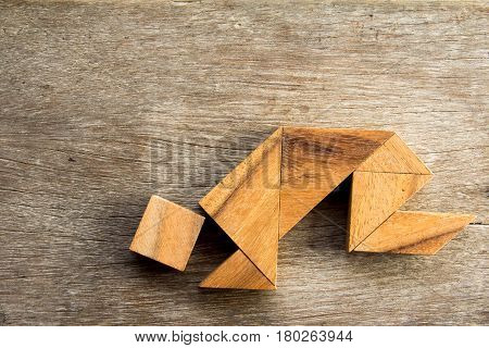 Wooden tangram puzzel in man crouch shape background