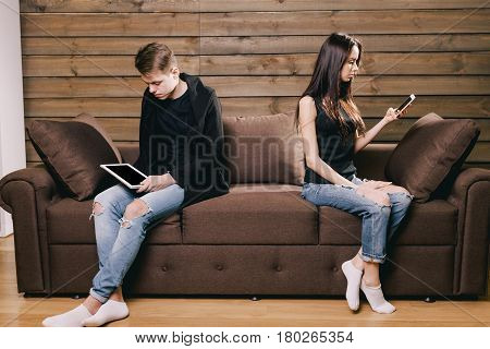 Husband and wife in a quarrel. They sit on a brown sofa and look at the tablet and phone. Concept of quarrel, divorce, mistrust