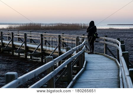 Young Woman Watching Sunrise On A Wooden Boardwalk With Bird Watch Tower In Early Morning