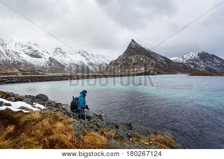 The photographer is walking on the hill of Lofoten islands winter time