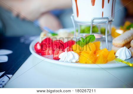 chocolate fondue with fruits in the blue pot, a delicious dessert