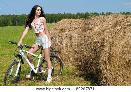 happy woman on bicycle in the field