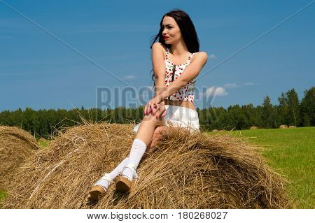 elegant brunette woman sitting on haystack outdoors