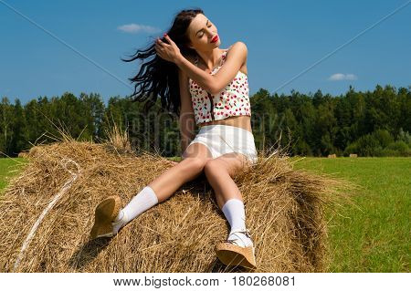 fashionable brunette woman sitting on haystack outdoors