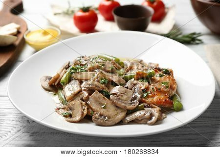 Chicken marsala with mushrooms and French beans on plate, closeup