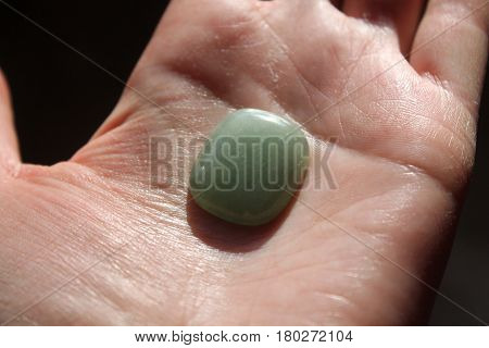 deep green color chrysolite crystal lay on the hand healing of the stones