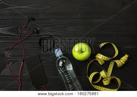 Athlete's set with bottle of water on dark background. Top view. Still life. Copy space