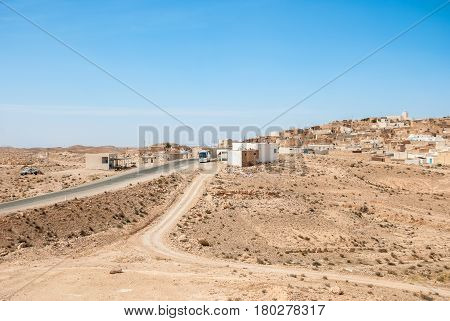 Highway in the desert passing through a small Arab town