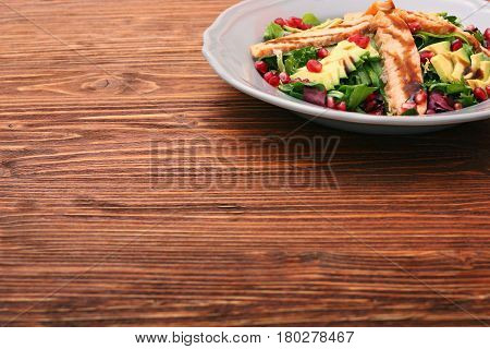 Salad with fried salmon, avocado and pomegranate seeds. Low fat healthy eating concept.