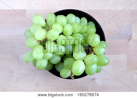 Lot of ripe green grape berries on bunche in black round bowl on wooden background top view close up