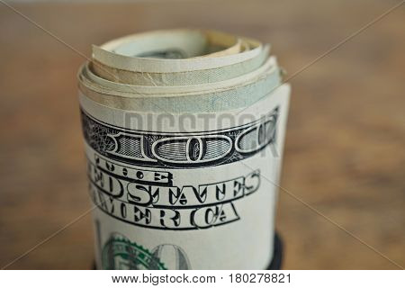 Macro detail of a green roll of American currency (USD, American dollars) with 100 dollars bank note on the outside as a symbol of plenty of money on the wooden background