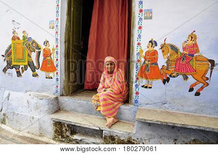Udaipur India september 12 2010: Old indian woman sitting in front of her huse on a ground with paintings on a wall.