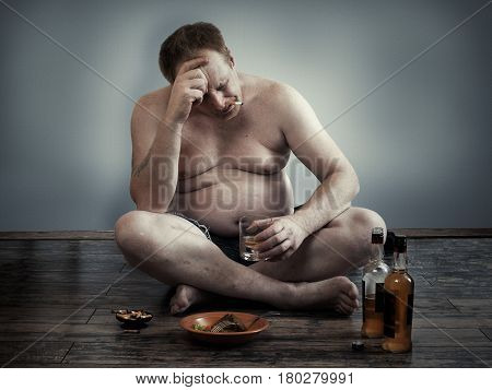 man with alcohol and a cigarette sitting on the floor. Habits lifestyle