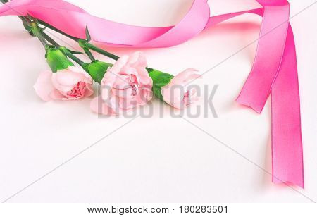 Three pink carnations with silk ribbon bouquet on white background Mother's Day card