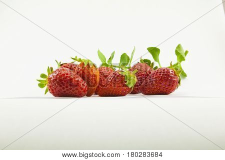 Strawberry field. An image of a juicy strawberry on a white background, as if a strawberry is drowning in cream or milk. A nice photo that pleases with its appearance.