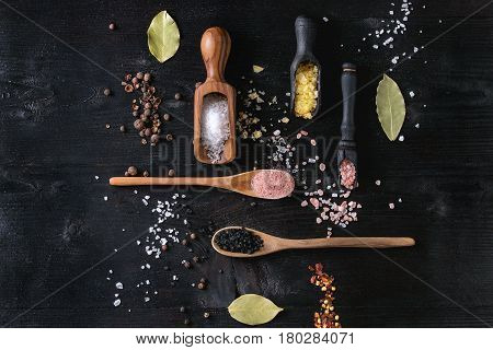 Variety of different colorful salt yellow saffron, pink, black himalayan, white sea and fleur de sel in wooden spoons with black, chili, allspice pepper over black burnt wood background. Top view