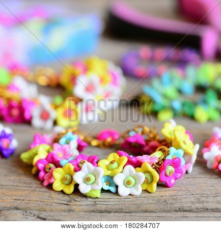 Set of beautiful bracelets on vintage wooden background. Bracelets made of colorful plastic flowers, leaves and beads. Summer accessories for a small girl