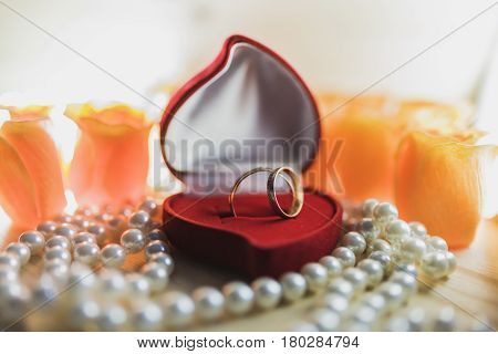 A pair of gold wedding rings with diamonds in a red velvet gift box in the form of a heart on pearl beads against a background of orange flowers.