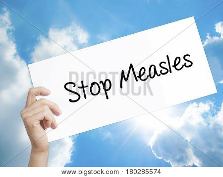 Man Hand Holding Paper With Text Stop Measles  . Sign On White Paper. Isolated On Sky Background