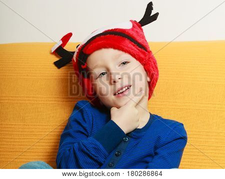 Christmassy decorations and accessories concept. Little boy sitting on sofa wearing red christmas hat with horns
