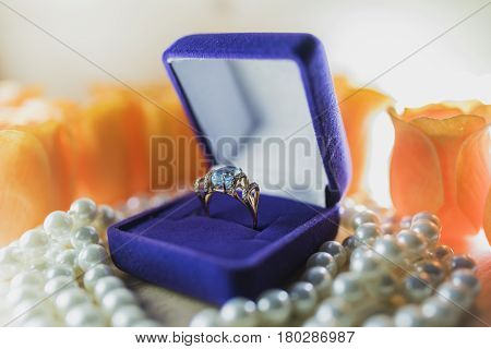 Bright gold ring with a large topaz in a lilac velvet gift box on pearls against the background of orange flowers